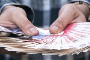 Working capital loan - man holding pound notes